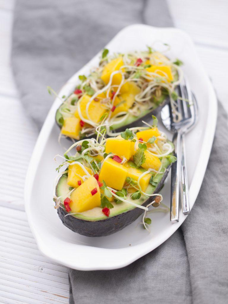 Mangowürfel mit Sprossen als Salat in Avocado serviert