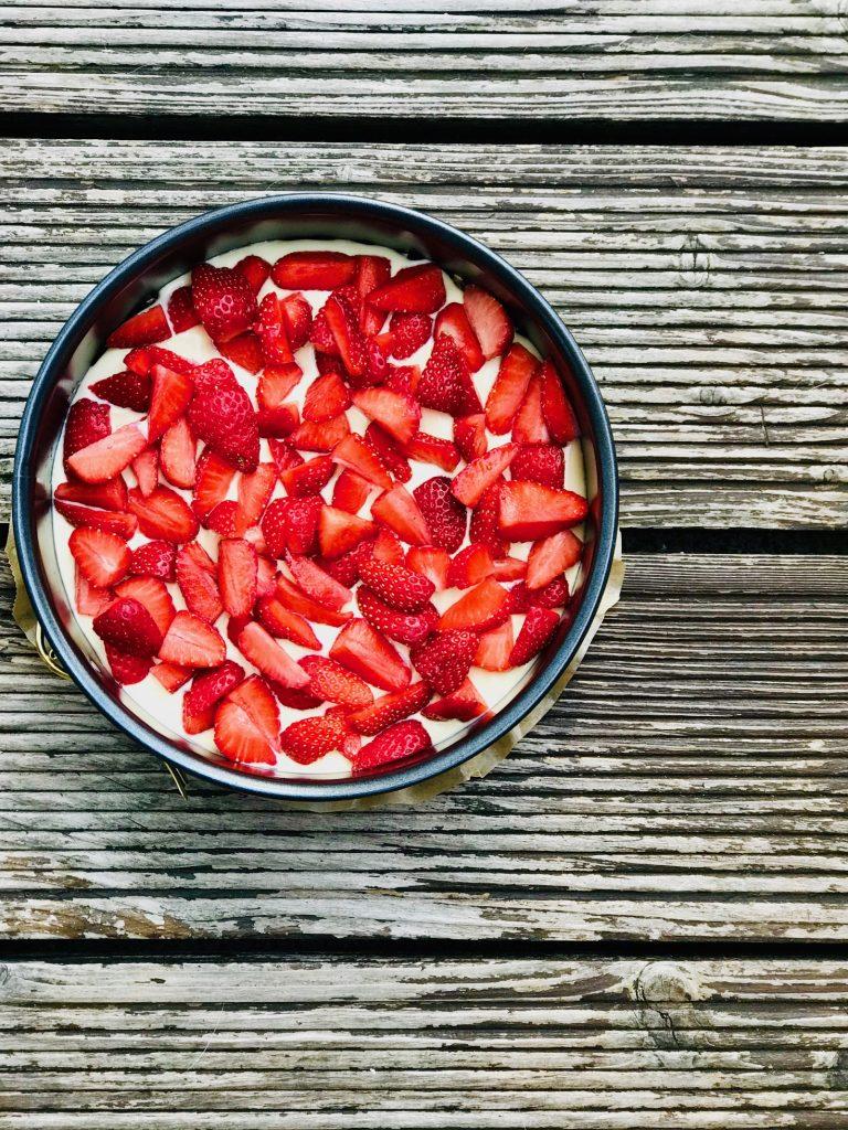 Low Carb Käsekuchen mit kleingeschnittenen Erdbeeren vor dem Backen