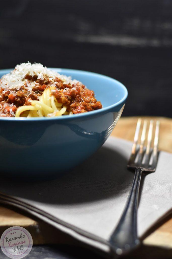 Champignon Bolognese mit Parmesan aus Spaghetti in einer blauen Schüssel angerichtet