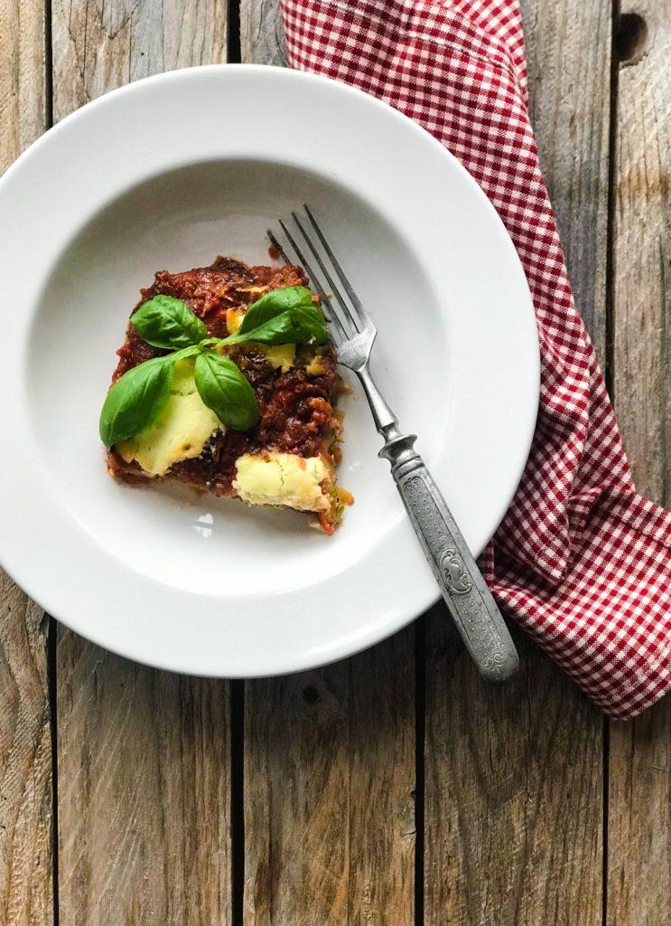 Parmigiana di Zucchine - Zucchiniauflauf, eine Portion auf weißem Teller