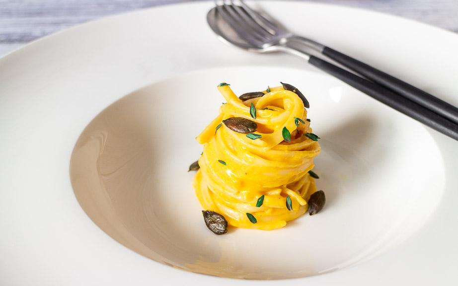 Cremige Pasta mit Kürbis Alfredo Sauce auf einem tiefen Teller