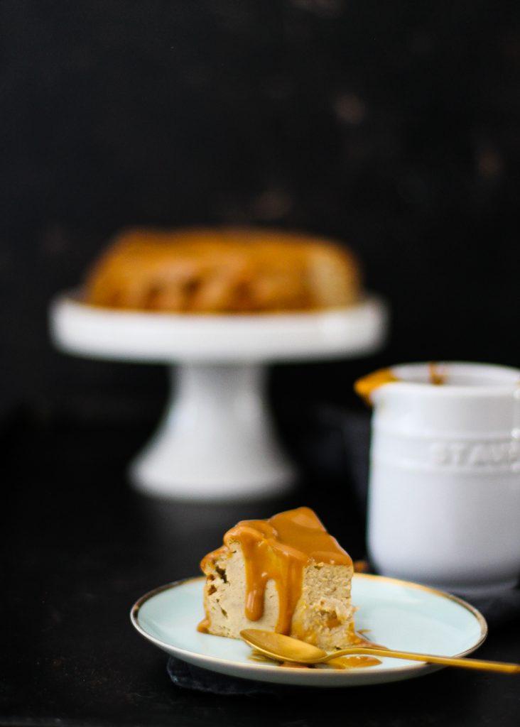 Käsekuchen auf einer weißen Tortenplatte, daneben ein Stück angeschnitten
