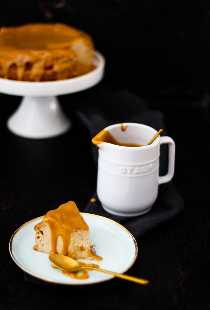 Käsekuchen auf einer weißen Tortenplatte, davor ein Stück auf einem Teller, daneben ein Milchkännchen mit Karamellcreme.