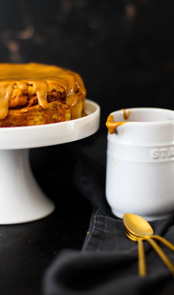 Käsekuchen mit Karamellcreme auf einer weißen Tortenplatte. Nahaufnahme.