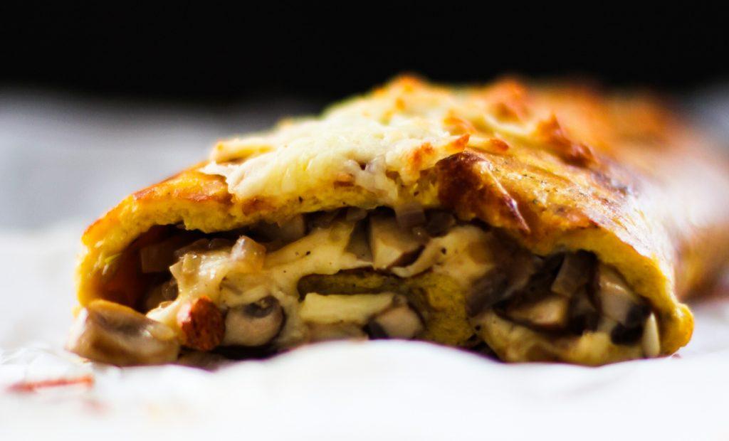 Rösti-Rolle Nahaufnahme gefüllt mit Käse und Pilzen