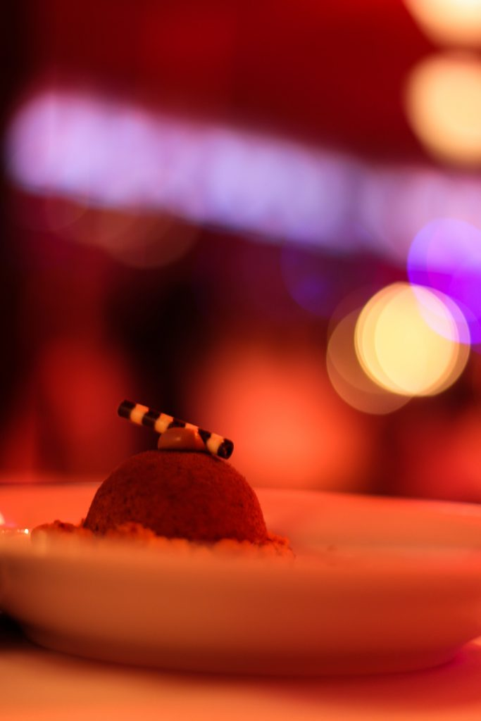 Nougateis auf einem tiefen Teller mit Schokoröllchen