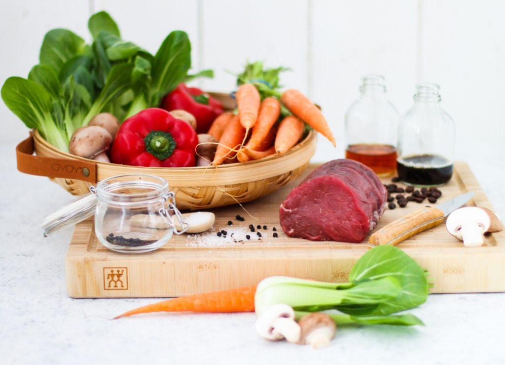Karotten, rote Paprika, Champignons und Pak Choi  in einem Korb und ein Stück rohes Rinderfilet.
