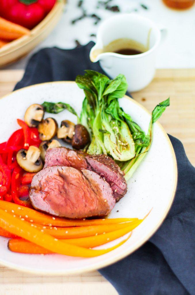 Gemüse und Scheiben rosa gebratenes Rinderfilet auf einem weißen Teller in Nahaufnahme mit Soße.