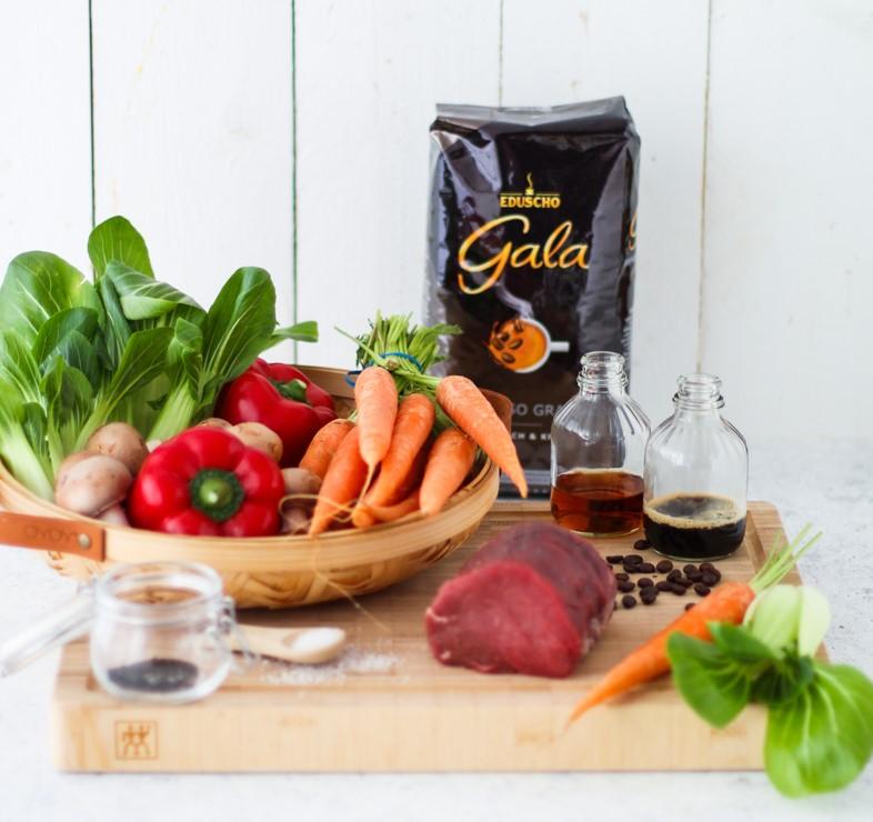 Gala von Eduscho Espresso Grande Packung, davor Gemüse in einem Korb und ein Stück rohes Rinderfilet.