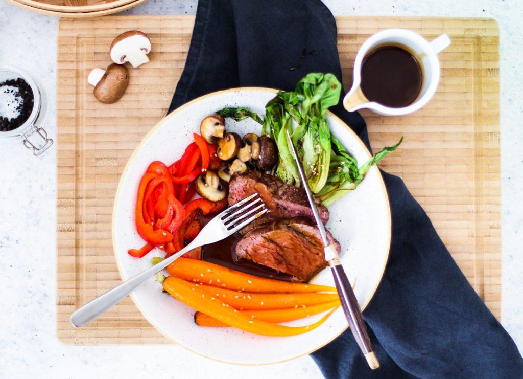 Gemüse und Scheiben rosa gebratenes Rinderfilet auf einem weißen Teller. Das Fleisch ist angeschnitten und das Besteck liegt auf dem Teller.