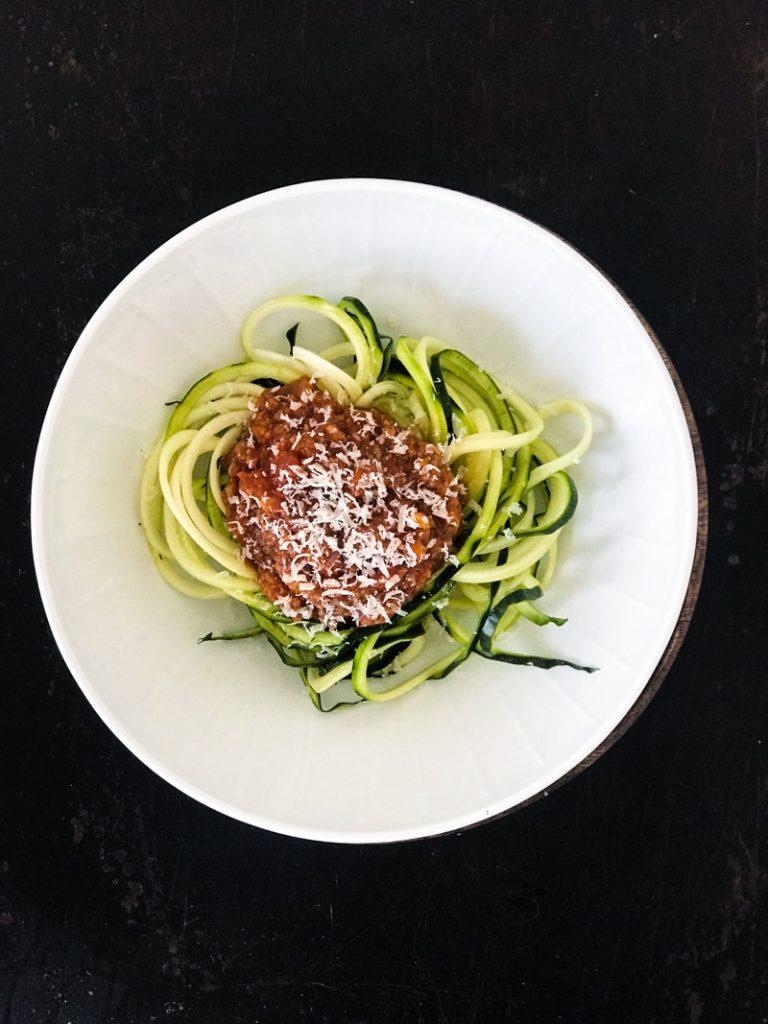 Vegane Bolognese aus dreierlei Pilzen auf Zucchininudeln im weißen Teller