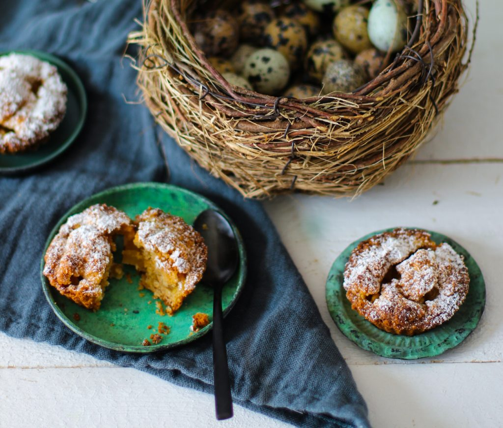 Apfelkuchen-Minis auf kleinen Tellerchen mit einem schwarzen Löffel und einem Wachteleier-Nest.