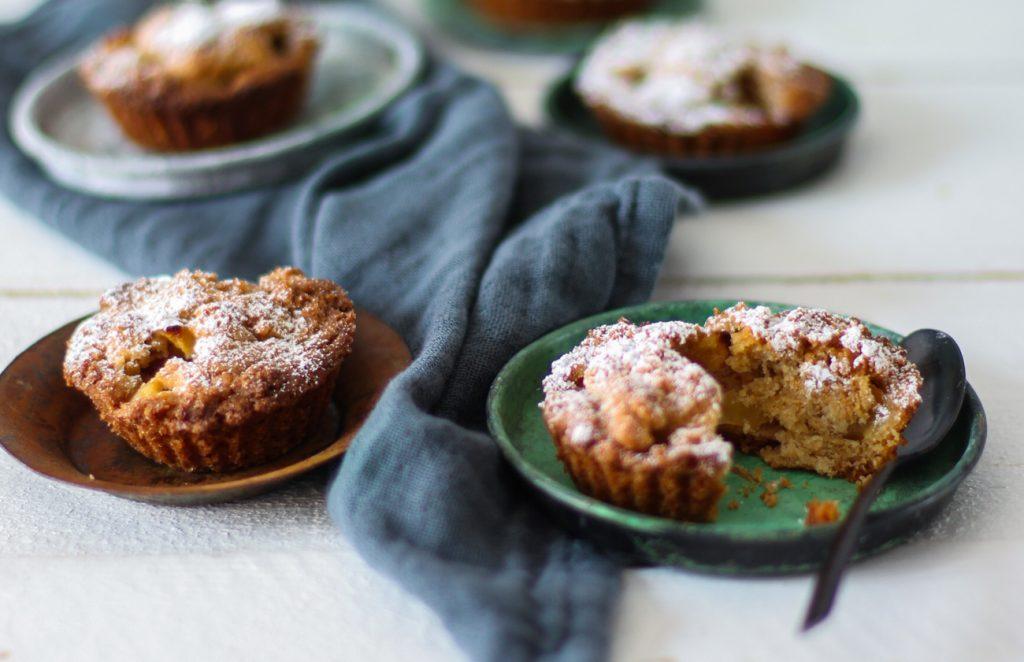 Apfelkuchen-Minis auf kleinen Tellerchen mit einem schwarzen Löffel.