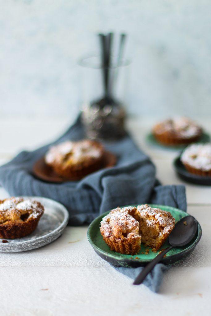 Apfelkuchen-Minis auf kleinen Tellerchen mit einem schwarzen Löffel., der ganze vorne in Nahaufnahme.
