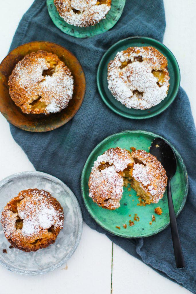 Apfelkuchen-Minis auf kleinen Tellerchen mit einem schwarzen Löffel von oben fotografiert.