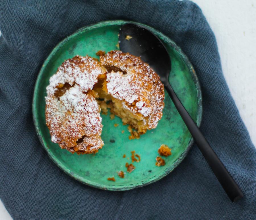 Apfelkuchen-Mini auf einem kleinen grünen Tellerchen mit einem schwarzen Löffel in Nahaufnahme.