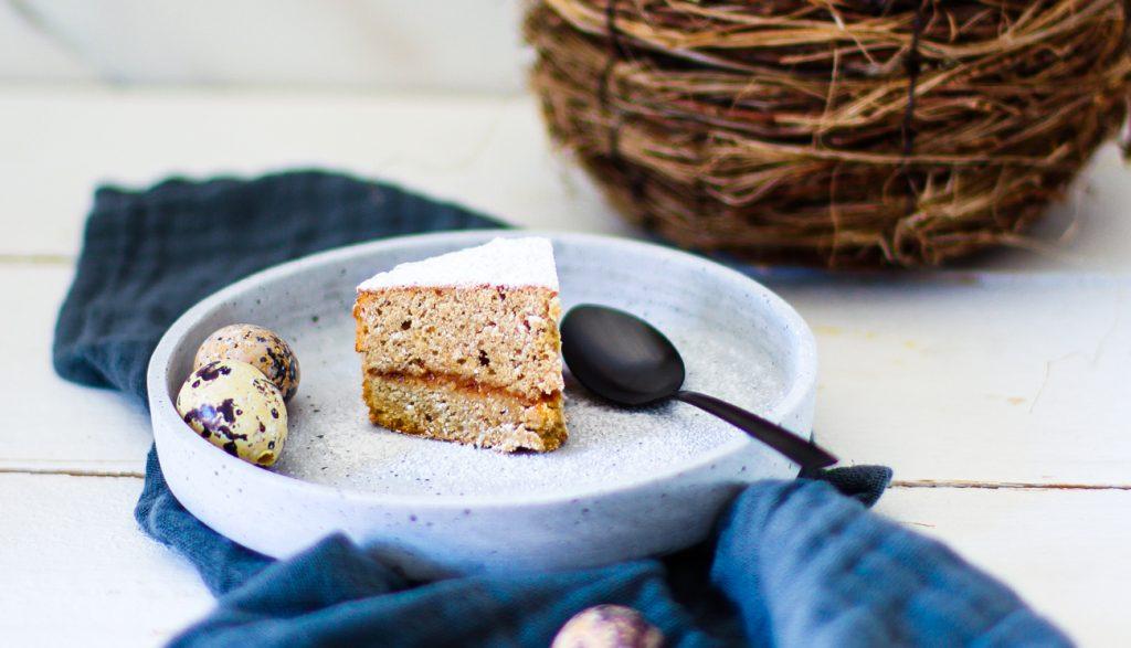 Low Carb Espresso-Kuchen ohne Mehl auf einem weißen Natursteinteller, daneben Wachteleier, darunter ein blaues Tuch