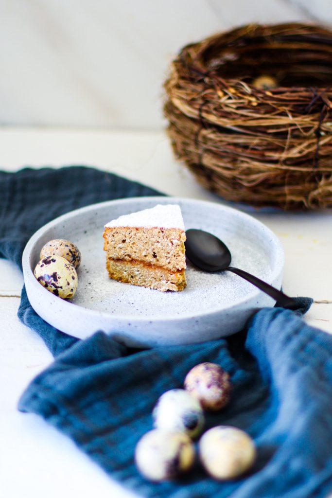 Low Carb Espresso-Kuchen ohne Mehl auf einem weißen Natursteinteller, daneben Wachteleier, dahinter ein Weiden-Osternest