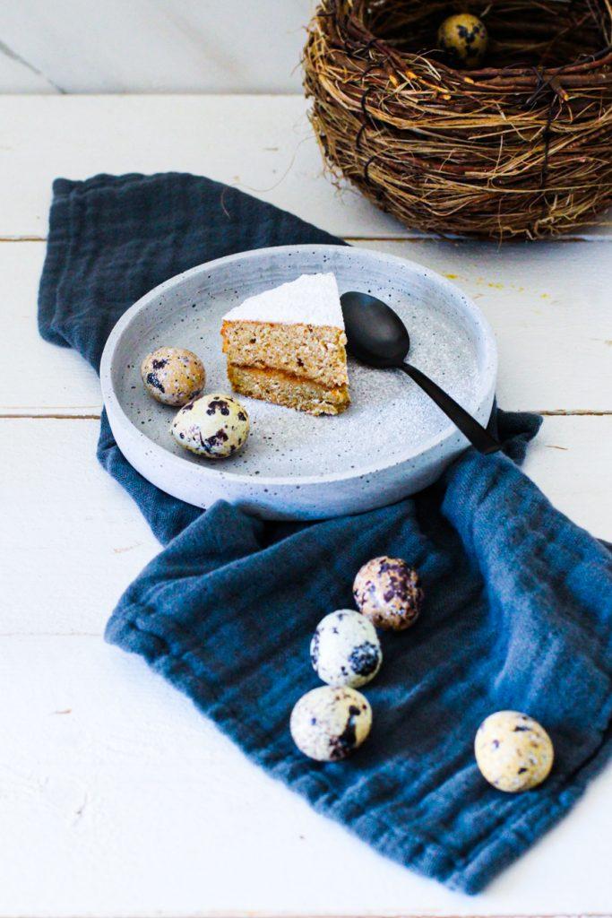 Low Carb Espresso-Kuchen ohne Mehl auf einem weißen Natursteinteller, daneben Wachteleier auf einem blauen Tuch