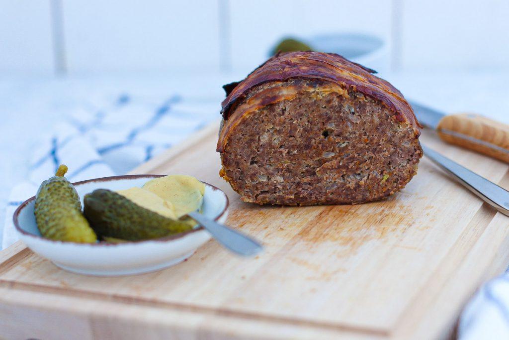 Omas Hackbraten mit Bacon obendrauf, aufgeschnitten auf einem Brett. Daneben Essiggurken und Senf.