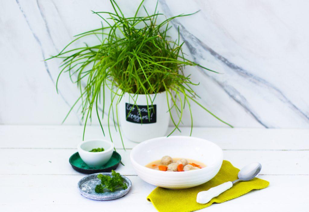 Bunte Gemüsesuppe mit Klößchen in einem weißen Teller vor einem Schnittlauch