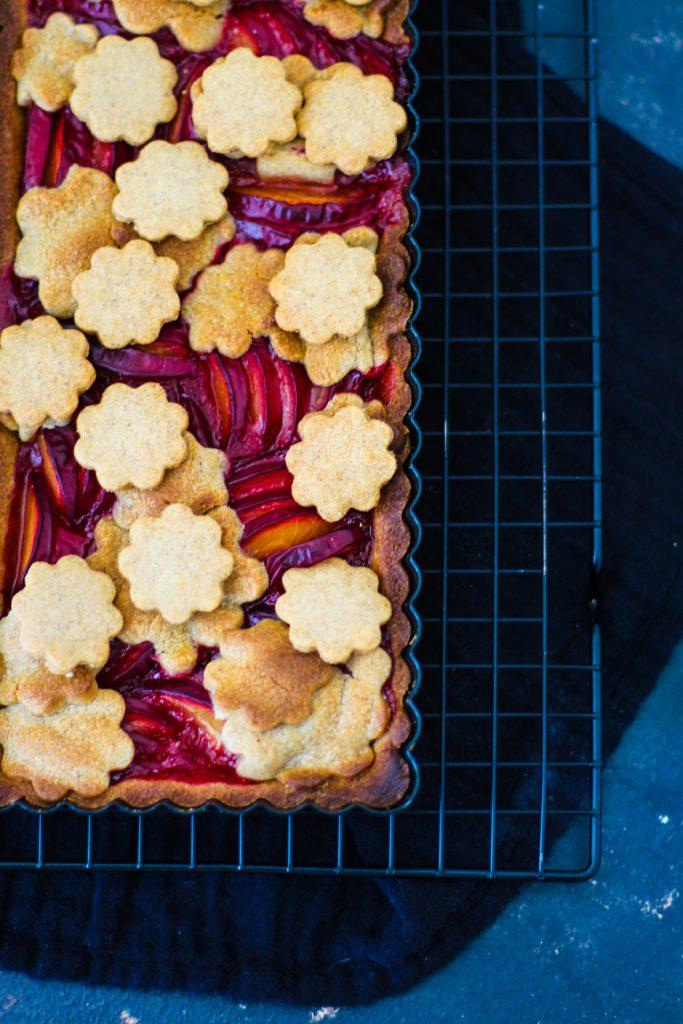 Mürbeteig Pflaumenkuchen mit Mürbeteigblumen auf einem schwarzen Gitter