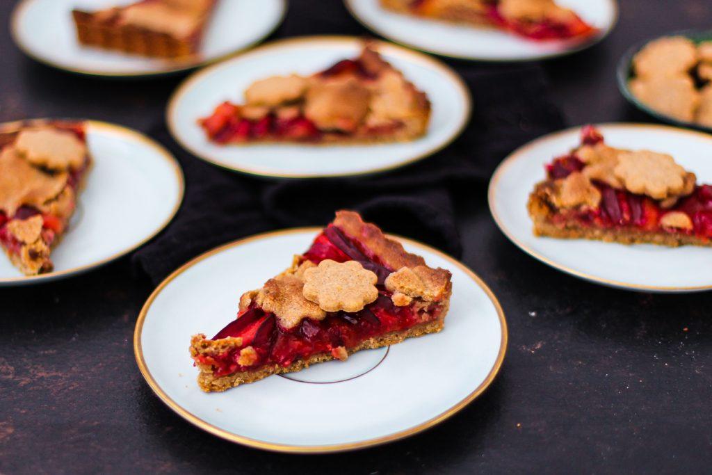 Mürbeteig Pflaumenkuchen mit Mürbeteigblumen, jedes Stück auf einem blauen Vintage Teller mit Goldrand
