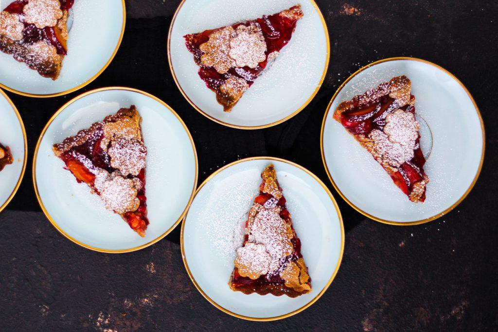 Mürbeteig Pflaumenkuchen mit Mürbeteigblumen, jedes Stück auf einem blauen Vintage Teller mit Goldrand und mit Puderzucker bestreut