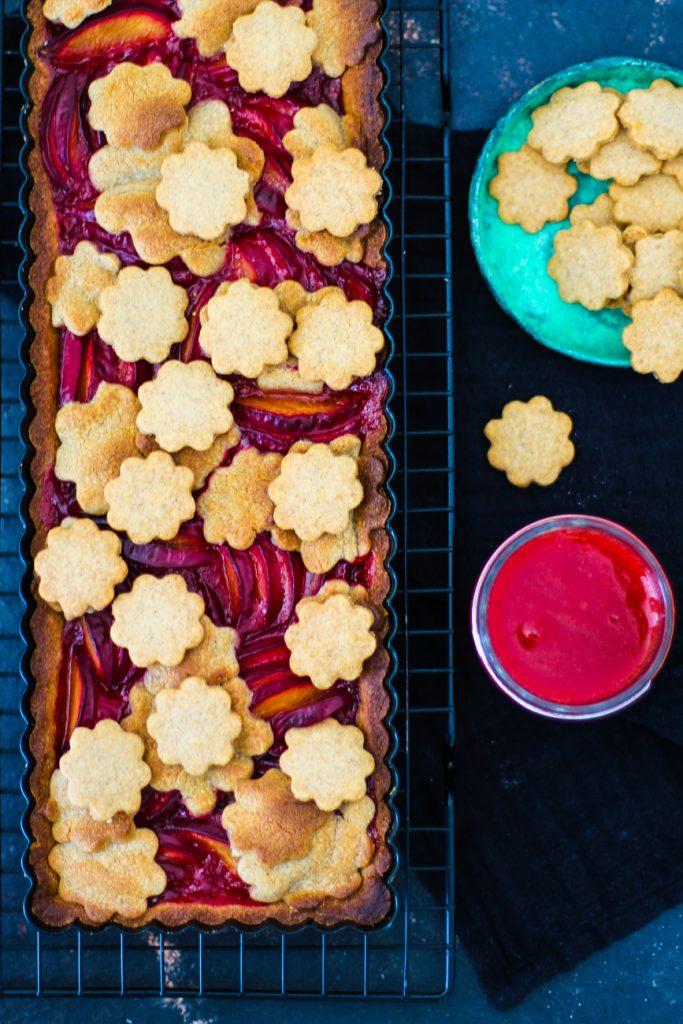Pflaumenkuchen auf einem Gitter, der Kuchen ist mit Blumenkeksen dekoriert