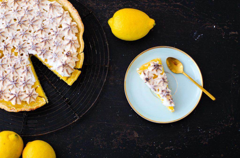 Ein Stück Zitronentarte auf einem türkisen Teller, daneben die angeschnittene ganze Tarte. Dahinter Zitronen.