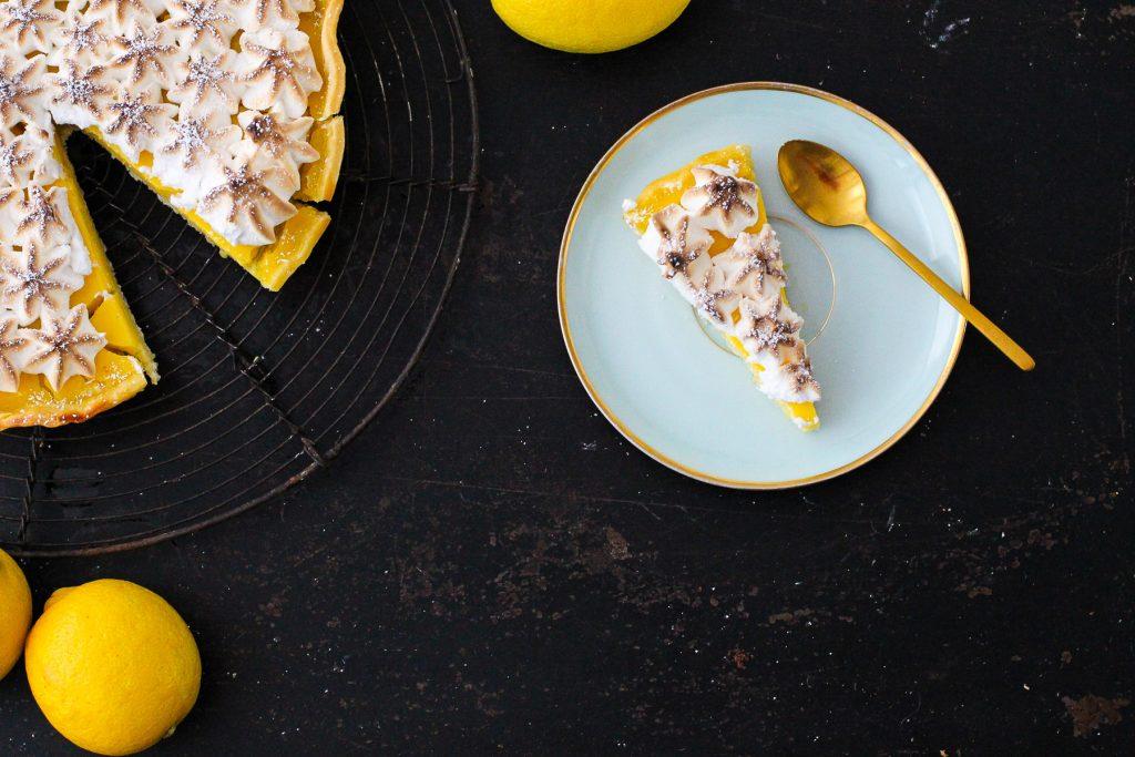 Ein Stück Zitronentarte auf einem türkisen Teller. Dahinter Zitronen und der ganze Kuchen.