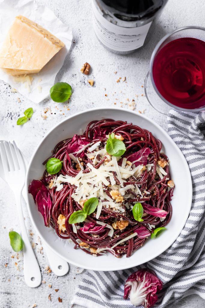 rote Spaghetti in einem weißen Teller, daneben ein Stück Parmesan und ein Glas Rotwein, von oben fotografiert