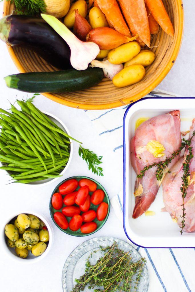 rohe Kaninchenkeulen in einer Schale mit Gemüse außerum