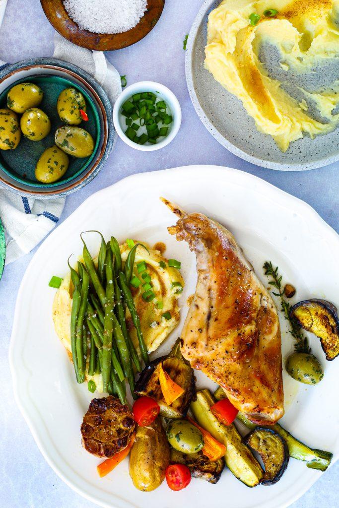 Kaninchenkeule auf Pastinakenpüree mit buntem Gemüse und Bohnen, auf einem weißen Teller, daneben ein Schälchen mit Oliven und eines mit Salz