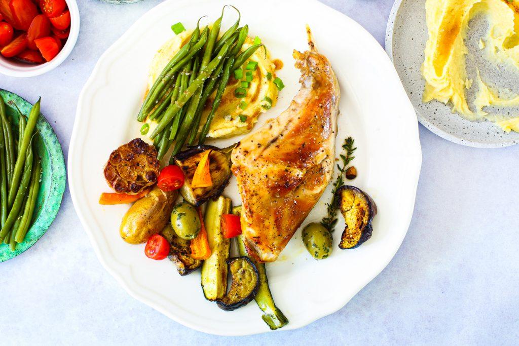 Eine Kaninchenkeule auf eine, weißen Teller mit Püree, Bohnen und Gemüse