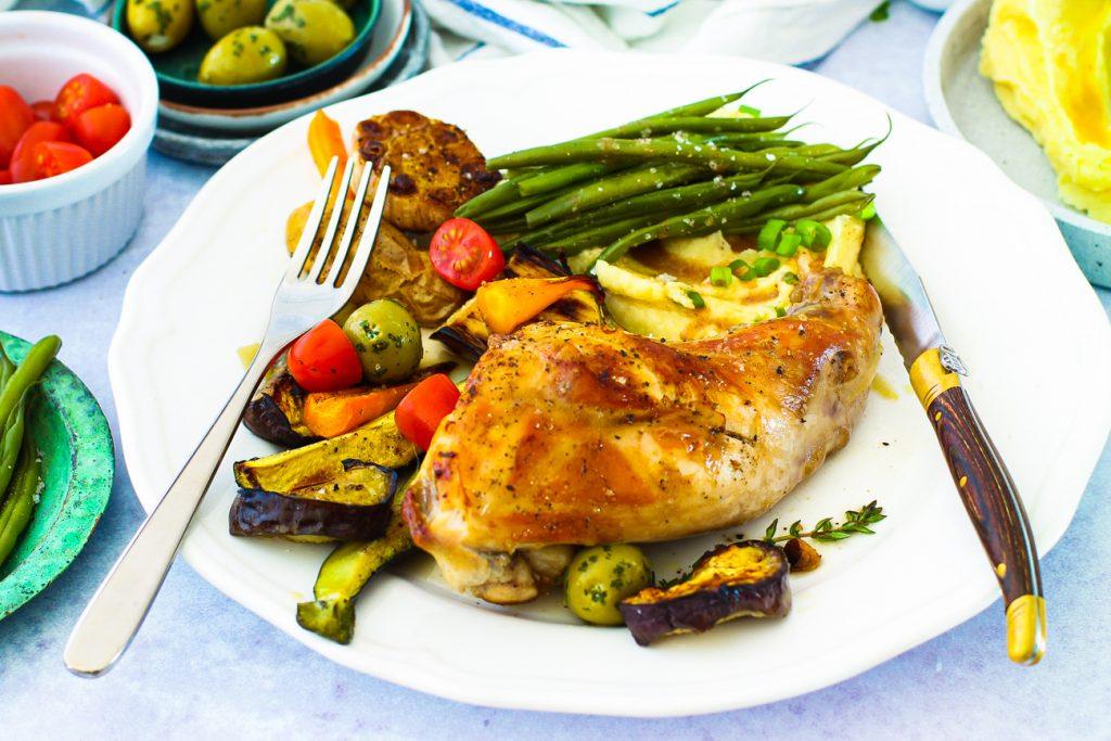 Nahaufnahme: Kaninchenkeule auf Pastinakenpüree mit buntem Gemüse und Bohnen, auf einem weißen Teller