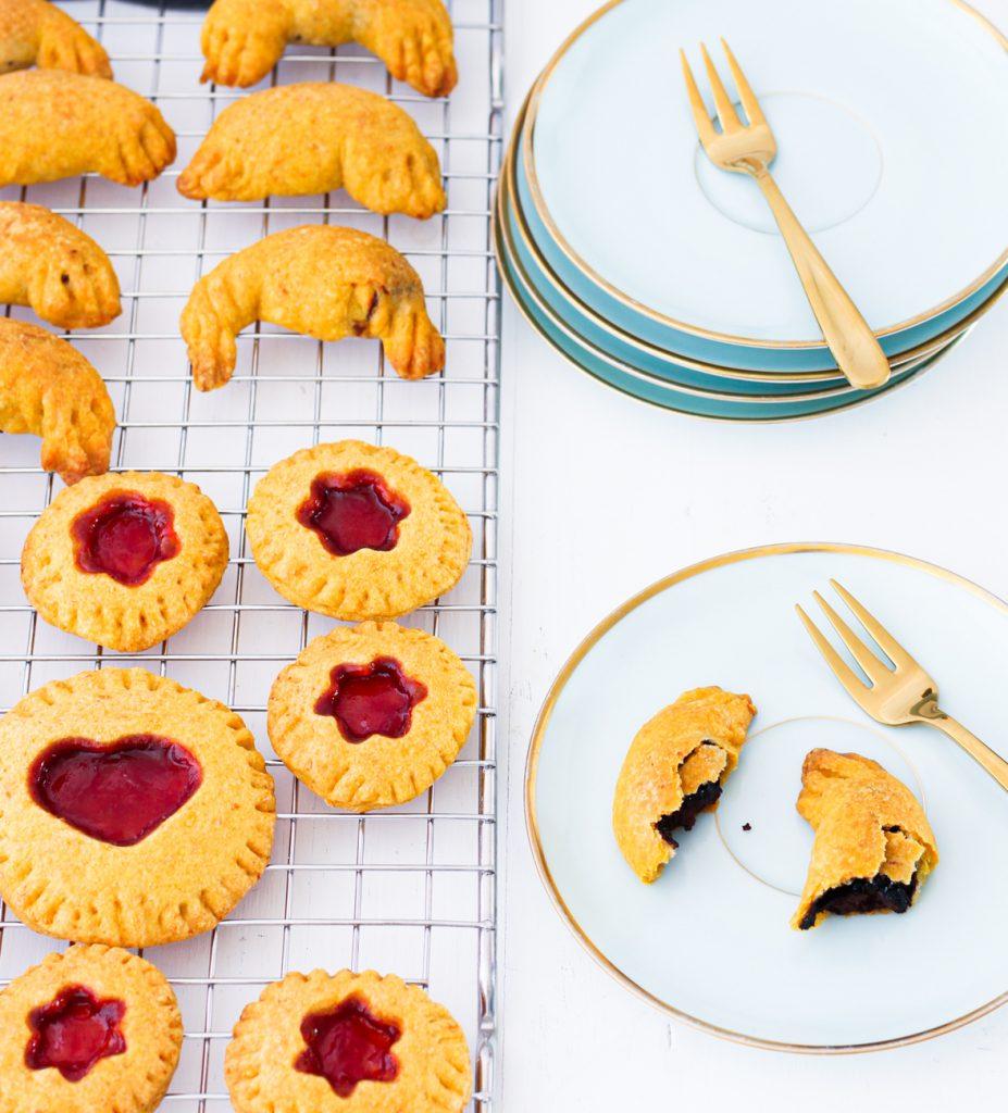 Kleine süße Hörnchen, Mini-Pies und Schnecken auf einem Gitter, daneben ein hellblauer kleiner Teller mit einem halbierten Schokohörnchen