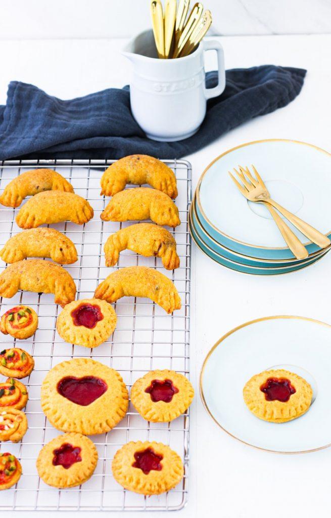 Kleine süße Hörnchen, Mini-Pies und Schnecken auf einem Gitter, daneben 2 goldene kleine Gabeln auf einem Stapel Dessertteller