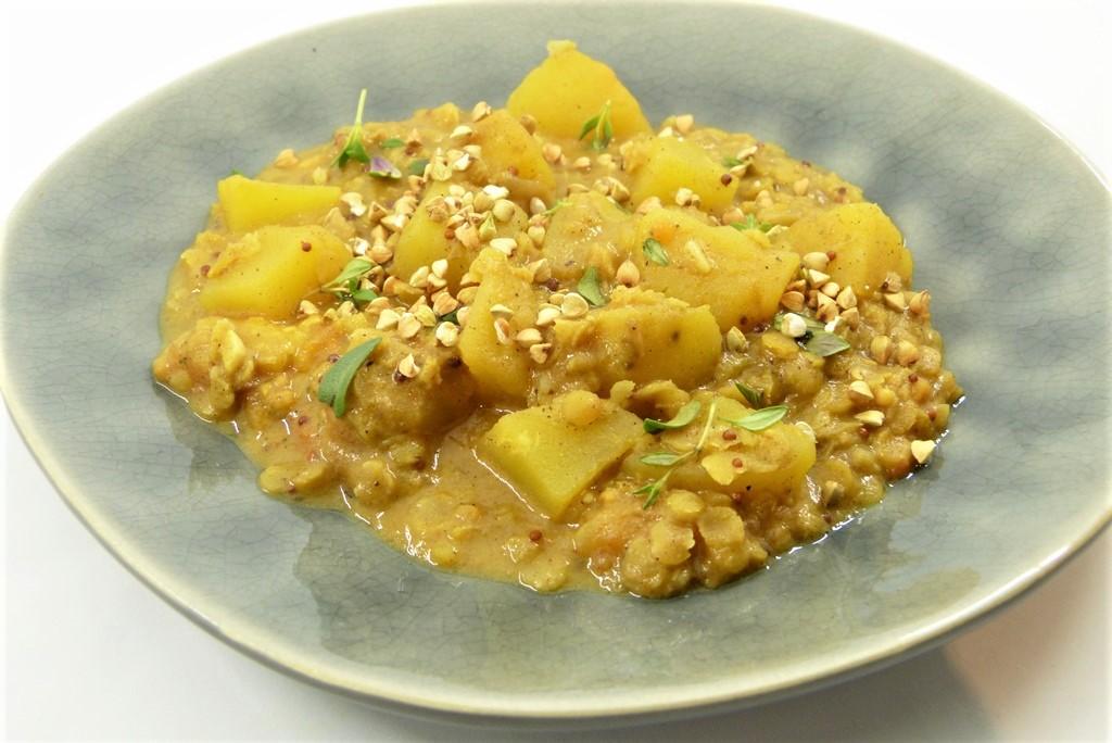 gelbes Kartoffelcurry auf einem hellblauen Teller