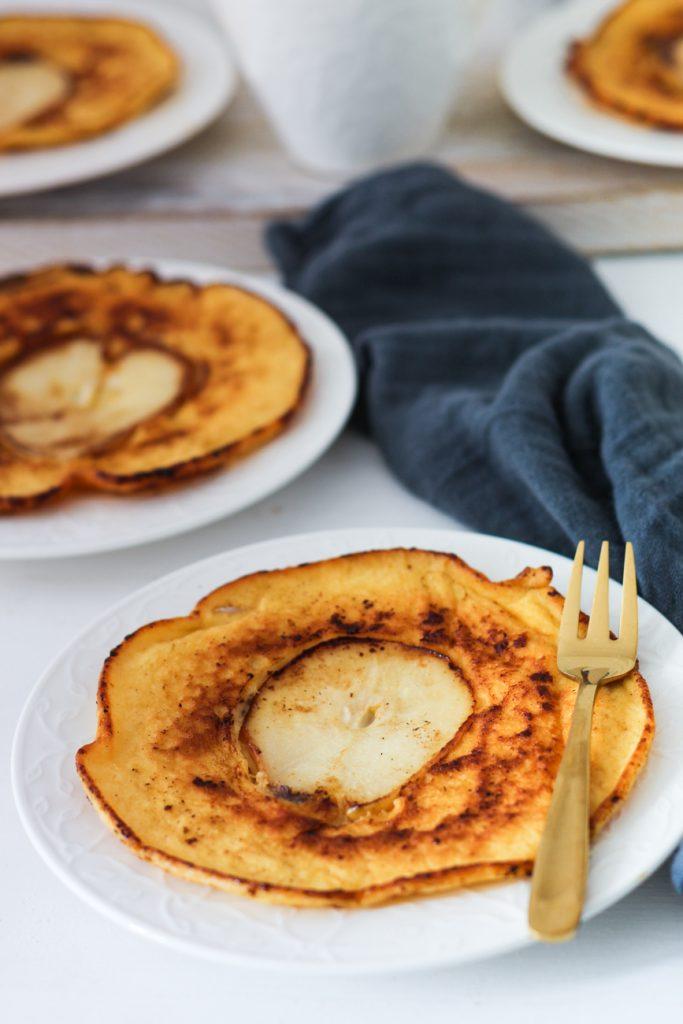 Pfannkuchen mit Birne in der Mitte, auf weißen Tellern