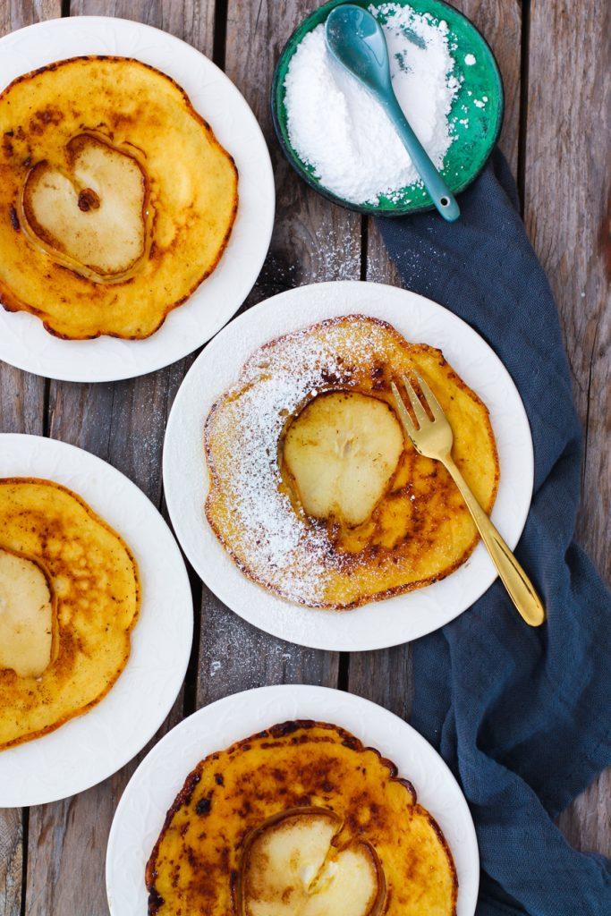 Vier kleine Birnen-Pfannkuchen auf weißen Tellern