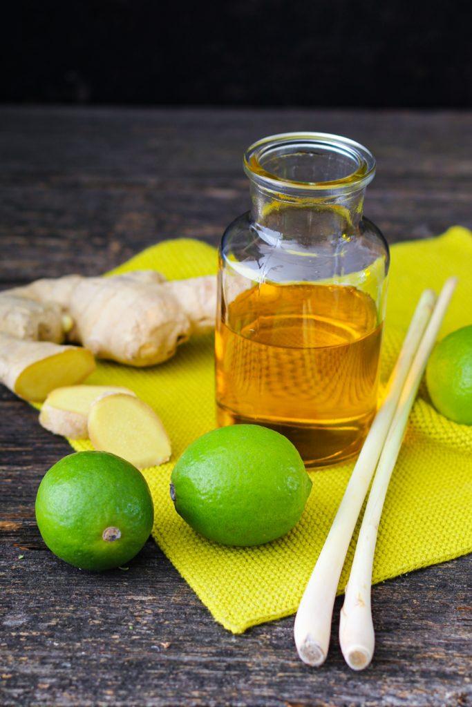 Ein Kännchen Öl, daneben Ingwer, Zitronengras und Limetten.