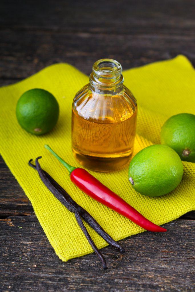 Ein Fläschchen Öl, daneben eine Chlilischote, Limetten und Vanillestangen.