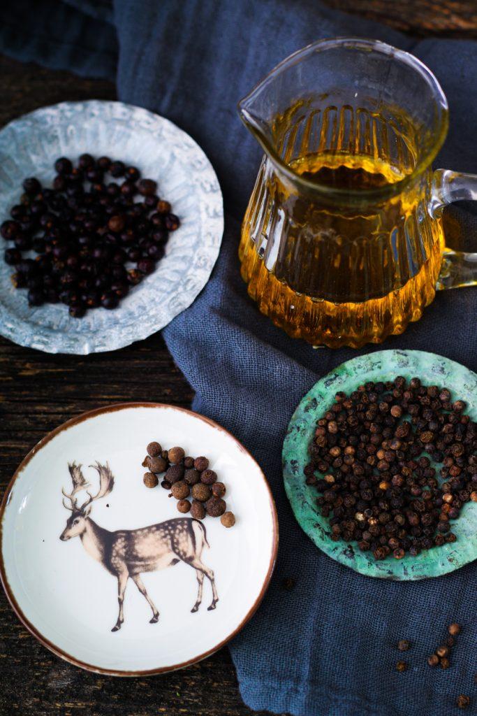 Ein Kännchen Öl, daneben kleine Tellerchen mit Pfeffer, Wacholder und Piment Körnern.