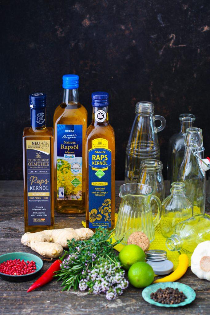 Rapsöl in Flaschen mit leeren Ölflaschen daneben. Davor Kräuter.