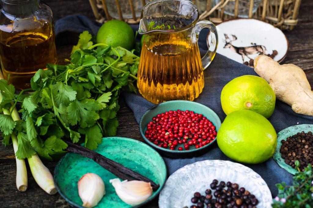 Kännchen und Fläschchen mit Ölen, rundum Kraüter und Gewürze.