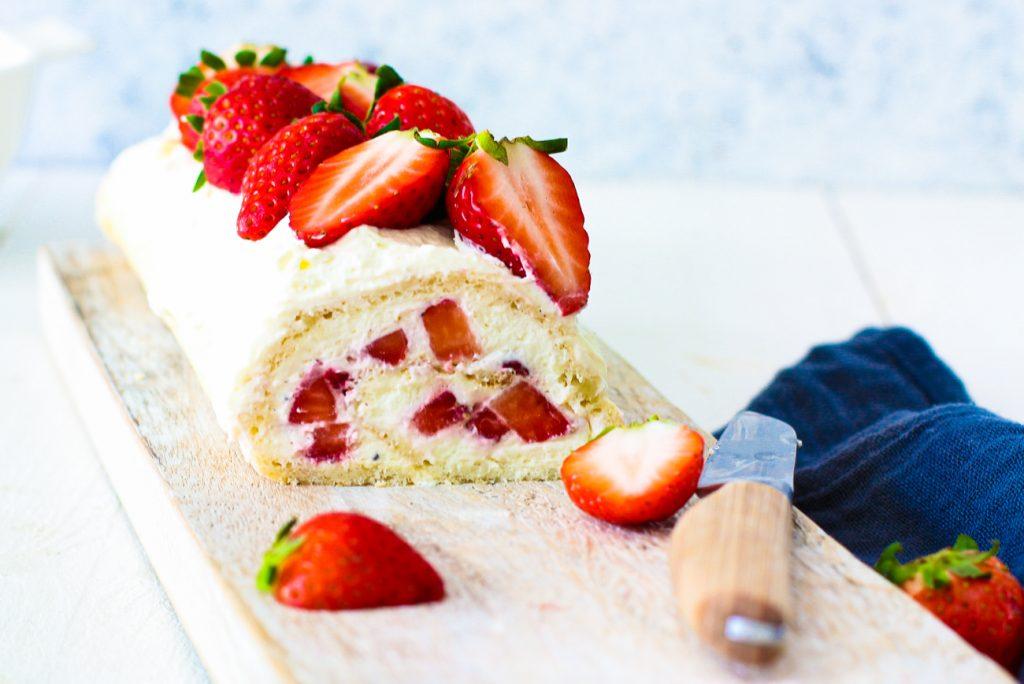 Erdbeer-Biskuit-Rolle aufgeschnitten auf einem weißen Brett