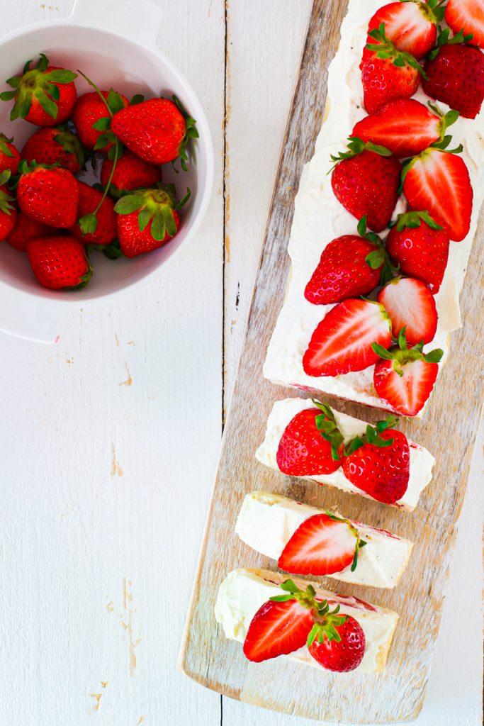 Erdbeerbiskuit von oben, daneben eine Schale Erdbeeren