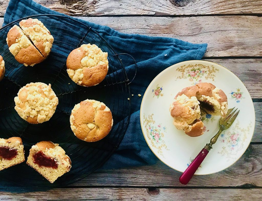 Muffins mit einem Erdbeerkern und Streuseln, einer aufgeschnitten auf einem kleinen Teller