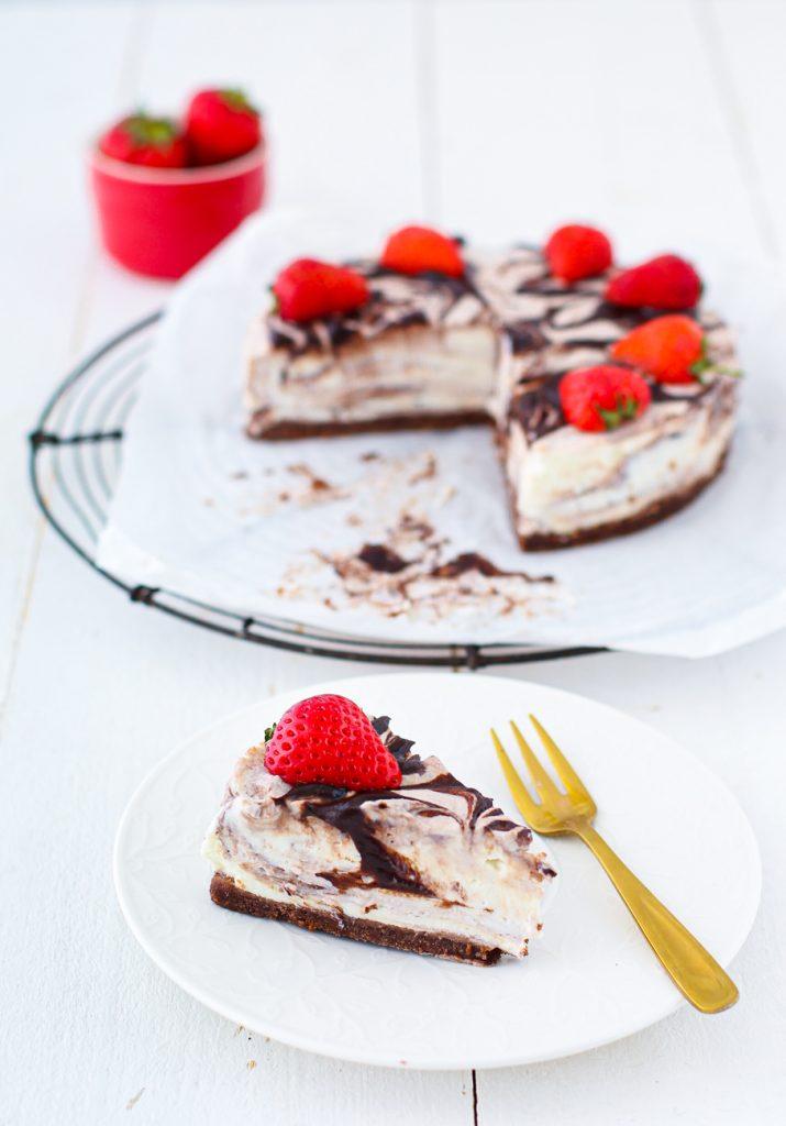 Cheesecake mit Schokoladenmarmorierung und Erdbeeren, ein Stücke auf einem Teller